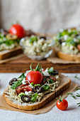 Broccoli paste with feta, olives and tomatoes on bread