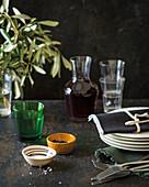 Italienische Tischszene mit Geschirr, Besteck, Pfeffer, Salz, Rotwein und Olivenzweigen