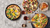 Verschiedene Pizzen (mit Trauben und Lachs, Ei und Bacon, Hackbällchen und Granatapfel)