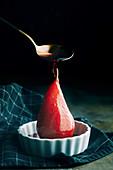 Rotweinbirnen in Stieilkasserolle mit Sirup begiessen