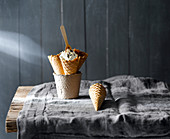 Mehrere Eistüten in Pappbecher und auf grauem Tischtuch