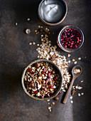 Frühstücksmüsli mit Nüssen, Granatapfelkernen und Joghurt (Aufsicht)