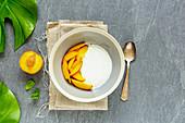 Natural yogurt bowl and fresh peach