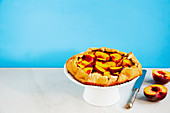 Homemade peach galette on blue background