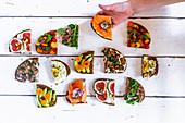 Halbierte, belegte Brote mit Gemüse, Parmaschinken, Champignons, Lachs, Feigen und Spiegelei
