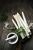 White asparagus, salt, pepper, parsley and a mortar on a wooden board