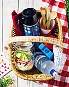 Picknickkorb mit Cäsarsalat im Glas