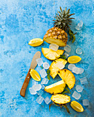 A pineapple, lemon wedges, and ice cubes