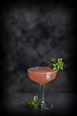 A Cosmopolitan cocktail decorated with herbs