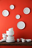 Weisses Geschirr auf Tisch und weisse Teller an roter Wand dahinter