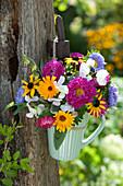Kleiner Strauß aus Sommerastern, Wicken, Ringelblumen und Sonnenhut in Tasse