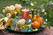 Kleine Sträuße aus Rosen und Goldrute mit Windlicht und Zierkürbissen auf Schale