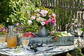 Strauß aus Rosen und Fenchelblüten mit Äpfeln und Birnen in Blechkasten