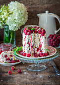 Vertical meringue roll cake with pistachios and raspberries