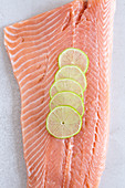 A side of fresh salmon with lemon slices