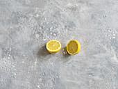 A halved lemon on a grey stone surface
