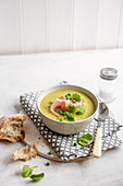 Pea and ham soup with pea shoots and bread