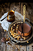 Hot chocolate with peanut caramel in a copper pan