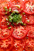 Tomato slices with salt, pepper and pesto (close-up)