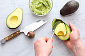 An avocado being scooped out