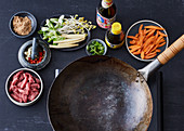 A stir-fry arrangement - a wok, meat, carrots, coriander and chilli