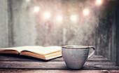 Kaffeetasse vor aufgeschlagenem Buch
