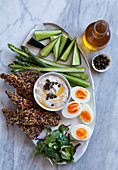 An appetizer platter with crackers, vegetables, eggs and a tuna fish dip (keto cuisine)