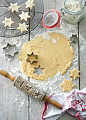 Cookie dough with cutters and a rolling pin on a floured wooden table
