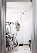 Ankleidezimmer in Weiß abgetrennt durch deckenhohe Vorhänge