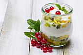 A layered dessert with yoghurt, mango, kiwi, mint and redcurrants