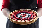 A woman holding a vegan berry pudding tart