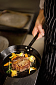 Rib eyed steak with chanterelle mushrooms and vegetables in a pan held by a chef