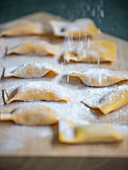Tortelli di zucca (pumpkin pasta, Italy) being dusted with flour
