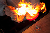 Flaming a cocktail with citrus fruit