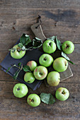 An arrangement of green organic apples on a rustic wooden table