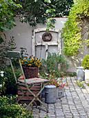 Stuhl neben Korb mit Sonnenhut, altes Fenster als Dekoration
