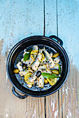 Marinierter Fisch mit Oliven, Zitronen und Gewürzen in Schale (Aufsicht)
