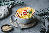 Turmeric and millet porridge with persimmon, orange and pomegranate seeds