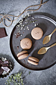 Chocolate macarons with golden spoons on a serving plate (top view)