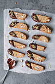 Lemon cantuccini with melted chocolate on baking paper (top view)