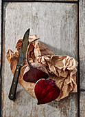 Halved beetroot on a board with brown paper and a knife