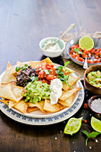 Mexican nachos with guacamole sour cream and pico de gallo