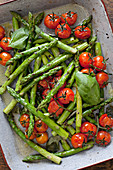 Asparagus and tomatoes topped with basil in a roasting tray almost filling the frame