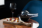 Cheese board on a table with a glass of red and a wine decanter