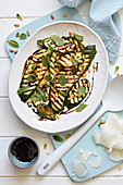Grilled courgettes covered with herbs and pine nuts