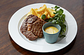 Steak and chips with hollandaise sauce served on the side