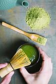 Matchatee mit einem Bambusbesen zubereiten