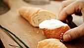 Hand entnimmt ein Stück Croissant mit Kräuterquark