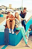 Eine Gruppe Jugendlicher mit Skateboard und modischer Kleidung entspannen