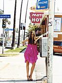 Junge brünette Frau in lila Sommerkleid und mit Sonnenbrille